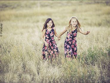 Zwei Mädchen laufen Händchenhaltend im Sommerkleid durch ein Kornfeld.