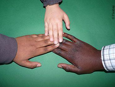 Drei Kinder unterschiedlicher Nationalitäten legen ihre Hände freundschaftlich aufeinander