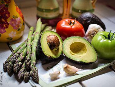 Gesunder Gemüseteller bestehend aus einer aufgeschnittenen Avocado, zwei ganze Tomaten in rot und grün, grünem Spargel und zwei Knoblauchzehen